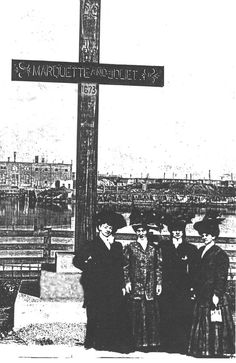 """Marquette & Joliet Cross  1907 · old photographs document an early mahogany cross where Robey Street [now Damen Avenue] ended, on the left bank of the W fork of the S arm of the Chicago River. It was designed by Thomas A. O'Shaughnessy and erected on Sept. 28, 1907, by the Willey Lumber Co., guided by the Chicago Historical Society. A tablet on the back side of its concrete base was inscribed: """"In memory of Father Marquette, S.J., and Louis Joliet"""