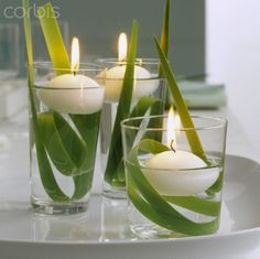 Spring decoration: three floating candles in glasses of water