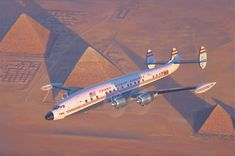 """Kalina - Through the Light of Ra - Oil -     This scene depicts a TWA Lockheed L1049G """"Super G"""" Constellation banking over the great pyramids of Giza near Cairo, Egypt, in the evening light."""