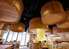 Huge wooden barrels traditionally used in the making of soy sauce are suspended over the heads of customers at this shop designed by Kengo Kuma.