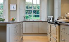 Beautiful light gray kitchen features inset cabinets adorned with round brushed nickel pulls alongside gray quartz countertops which frame a cream Aga Range.