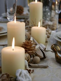 A scattering of seed pods, pinecones and nuts surround cream pillar candles for this easy centerpiece. Its neutral colors work with the table's subdued palette.