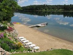 A gorgeous sandy beach surrounded by gardens at the Half Moon Trail Resort in Park Rapids, MN. #OnlyinMN
