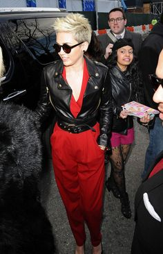 Miley Cyrus Clothes A black leather motorcycle jacket with gold zippers and attached belt for a somewhat edgy look while attending New York Fashion Week. Brand: Moschino Yes I would wear this edgy and sophisticated but not trashy