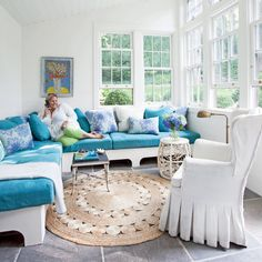 Cheery Sunroom - The homeowner uses her sunroom to curl up with a book or hang with friends, so comfy seating was a must. She had only an 11- by 13-foot area with which to work so she had her contractor build two benches for a space-saving and less expensive option than a sectional. She kept the room cheery and bright with fresh white paint on the walls and ceiling and bright blue cushions.
