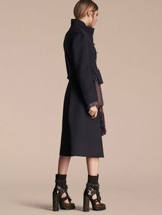 A dark navy deftly crafted Burberry military tailcoat in structured double wool with artisanal details and round shank buttons. The cut-out corset-inspired peplum highlights the waist, while puff shoulders and a stand collar create a pronounced silhouette.