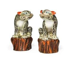 A Rare Pair of Kakiemon Models of Tigers. Edo Period (late 17th century). Decorated in iron-red, yellow, blue and black enamels, the characterful animals seated on treestump bases decorated in a dark brown glaze