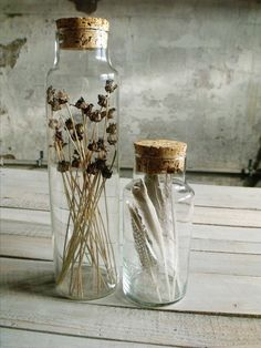 corked jars filled with dried flowers and feathers