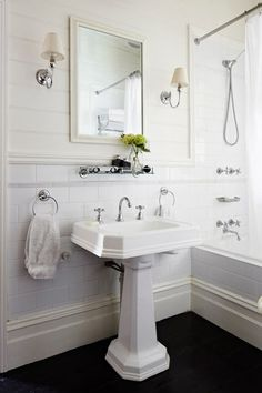 Classic white bathroom design with tongue and groove panels paired with large subway tile backsplash framing ivory beveled mirror flanked by single sconces with pleated shades and vintage glass shelf over pedestal sink. Classic White Bathrooms, Classic Bathroom, Modern Bathroom, French Bathroom, Bathroom Small, Downstairs Bathroom, Simple Bathroom, Interior Exterior, Home Interior
