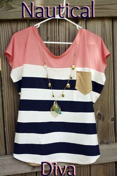 Coral with navy and white stripes, tan pocket and a long, delicate necklace. Cute!
