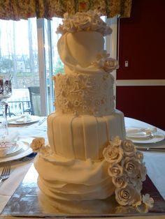- German chocolate wedding cake.  All white wedding cake. Roses made out of gum paste. Piping on second tier