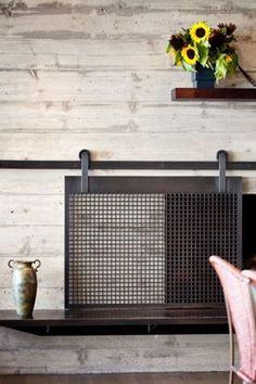 A sliding barn-door fireplace screen?  Neat. Via Porch.com