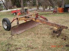 Grader - Homemade grader intended to be pulled behind a tractor. Constructed from a surplus scraper frame and an 8' blade. Mounted on a pair of repurposed cultivator wheels.