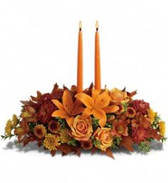 Family Gathering Centerpiece T169-1A - As your loved ones gather around the table, they'll bask in the warm glow of two orange taper candles surrounded by a fantastic array of fall flowers.  (teleflora images used with permission)  $47.95