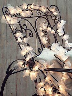 Iluminada por luzinhas envoltas em organza, a cadeira de ferro é pura delicadeza. Pisca-pisca Villa Pano, cadeira Dom Mascate