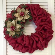 This pretty wreath says Christmas very simply and without too much fuss.  The base wreath is made with red burlap jute material. It is finished with 2 burlap Christmas ornaments that loosely resemble flowers with holly berries and greenery. This burlap wr