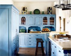 """DISTRESSED """"I wanted this jolt of color to emphasize that the kitchen is the joyful heart of the house,"""" explains designer Christina Rottman. To achieve that vintage blue, a blackened umber glaze was applied to the cabinets, then painted over with a turquoise glaze. Buffing, stippling, and scraping complete the timeworn look. Click through for more kitchen cabinet ideas."""