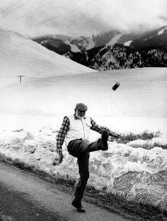 Ernest Hemingway kicks a can, I can tell this was taken in Sun Valley, ID - Bald Mtn is in the background. Today there is actually a memorial to Hemingway on the same road he's walking on in this photo.black and white photos