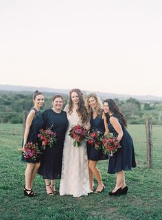 Beautiful bride in lace with gorgeous bridesmaids in black dresses and red bouquets   www.onefabday.com