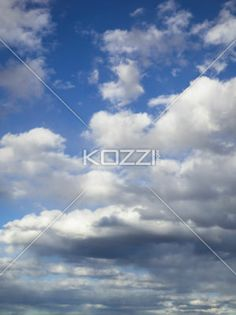 vertical image of cloudscape. - Vertical shot of white clouds against blue sky.