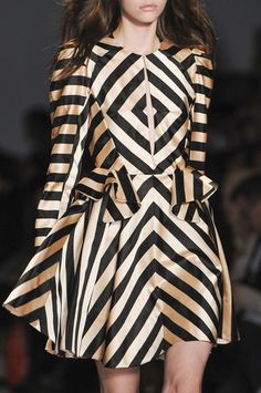 SYMMETRICAL #2  In this image the garment details of black geometric stripes are identical on each side of the garment, giving it a symmetrical shape.