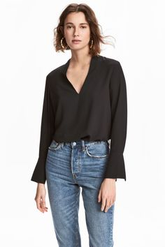 Black. V-neck blouse in woven fabric. Long sleeves with wide, flared cuffs with slit. Rounded hem with slits at sides.