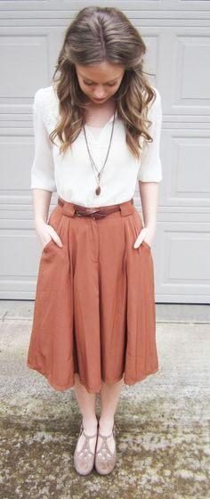 White blouse, burnt orange skirt with skinny leather belt and neutral flats.