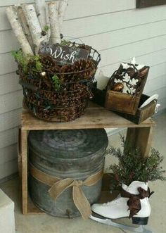 Front porch decor.  Vintage treasures from the barn where I grew up; wooden boxes, weathered boards, covered tin, and a wire basket.  Add in ice skates, evergreens, birch branches, white twinkle lights, wooden ornaments,  jingle bells, pine cones, little festive signs, and some rustic ribbon to bring it all together for the holiday season.