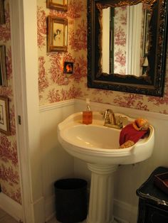 red toile wallpaper & dark wood frame on mirror contrasting with white fixture.