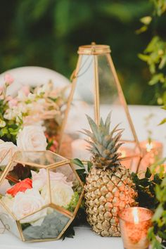 Wedding centrepiece with a modern lanterns, terrariums for flowers and a gold pineaples!