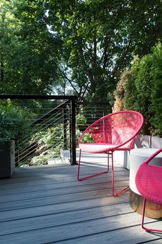 "The wooden backyard deck was replaced by a new deck with cable railing. Bright poppy chairs from <a href=""http://www.industrywest.com/"" target=""_blank"">Industry West</a> make a statement."