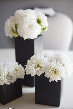Wonderful color contrast of simple white blooms in small black vases.  Simple, clean, yet still soft and romantic.  Yes. #feelbeautiful #whbm