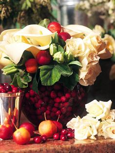 Fruit Frugal. Stretch your floral arrangement budget by adding in cheap, plentiful cranberries. Crab apples on skewers, delphiniums, cranberries, white calla lilies, and roses give this arrangement a fanciful look.