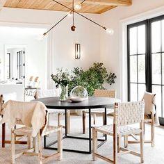 dark round dining table, modern light fixture, dark french doors, light unique modern chairs