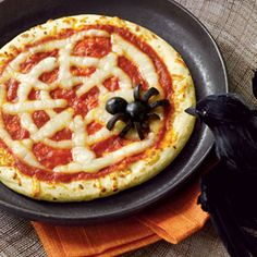 Spiderweb Pizza - Womans Day, Pepperoni pizza with strips of string cheese for a web and an olive spider! Super cute!