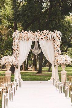 O lustre complementa a decoração do arco e é perfeito para uma decoração de casamento com voal.