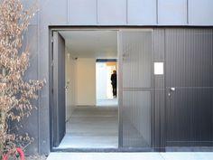 Un long couloir pour desservir les trois logements - Maison noire en Belgique