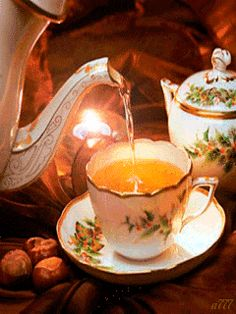 A warm and cozy gif of tea being poured from a teapot into a fine Christmas china cup in front of a flickering candle.