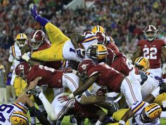 LSU Tigers running back Leonard Fournette (7) leaps over Alabama Crimson Tide defense during the fourth quarter at Bryant-Denny Stadium. Alabama won 30-16.  Marvin Gentry, USA TODAY Sports
