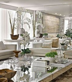 Mirrored walls & coffee tables combined with silver accents make this all white space sparkle