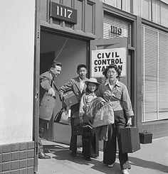 A social worker at a Wartime Civil Control Administration station directs a family to the waiting bus, photographer Dorothea Lange, May 6, 1942, Oakland, California.