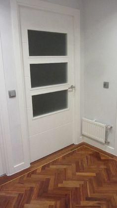 Puerta abatible acristalada de salón, lacada en blanco, diseño con tres vidrio de cristal traslúcido.
