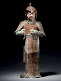 Chinese terracotta figurine of a Tang Dynasty (618 - 906AD) warrior with left arm holding the top a shield.