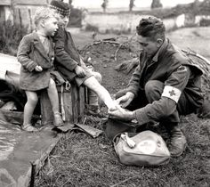 A medic treats the burned leg of a French boy, June 1944. KEN BELL, LIBRARY AND ARCHIVES CANADA—PA141703