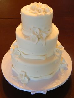 Three tier fondant covered wedding cake with handmade gumpaste calla lilies and sugar pearl accents