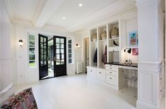 More open mudroom with white linoleum floors. Storage lockers extend into a small study area.