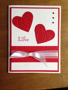 Used Stampin-Up Real Red and Whisper White cardstock. Stampin- Up Heart Punch; then embossed hearts using the Anna Griffin Rosa embossing folder. Used the Stampin-Up dotted Swiss embossing folder on the red strip. With Love is from the Stampin-Up Field Flowers set. Ribbon is from Jo-Ann's and brass are from Michaels.