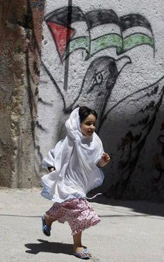 """nixon-baba: """" """" kitaab-e-dil: """" eastlondoner: """" A girl runs past a Palestinian flag spray painted on a wall in the Balata refugee camp, near the West Bank city of Nablus May Palestine History, Israel Palestine, Palestine Quotes, We Are The World, People Of The World, Islamic World, Girl Running, Islamic Pictures, Children"""