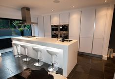 This contemporary high gloss island kitchen design is finished in a Polar white high gloss satin lacquer. The Polar white is sharper than other whites and in this design lighting integrated within the breakfast bar effectively shows off its crisp and slee Kitchen Installation, Kitchen Layout, Open Plan Kitchen, White Kitchen Design, Contemporary Kitchen, Modern Kitchen, London Kitchen, White Kitchen Island, Handleless Kitchen