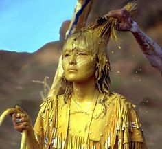 Apache girl at the Sunrise Ceremony (na'ii'ees), a coming-of-age rite. Girls being initiated into womanhood are painted with a sacred mixture of corn pollen and clay (or sometimes cornmeal and cattail pollen). This is the blessing phase of the long celebration. The pollen is considered to be holy, a symbol of life.   https://sphotos-a.xx.fbcdn.net/hphotos-ash3/62834_439239522831873_1407305655_n.jpg